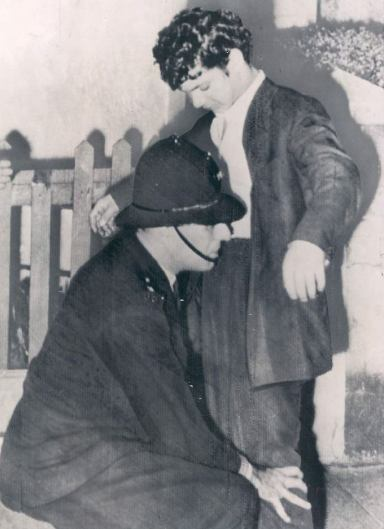 Some real-life police work in 1958: A policeman searches a teddy boy during the Notting Hill riots.